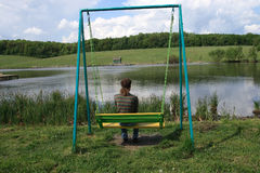 Young man siting on swing bench Royalty Free Stock Photography