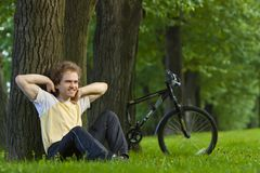 Young man siting under the tree near his bycicle Stock Photos