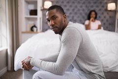 Young man siting while woman resting on bed at home Stock Image