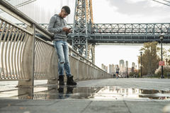 A young man sits and admires the view of NYC`s Williamsburg Brid Royalty Free Stock Image