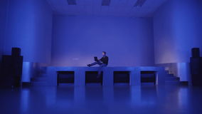 A young man sits alone on an empty dance floors and uses laptop to invite friends to a party. A young man sits alone on an empty dance floors and uses laptop stock footage