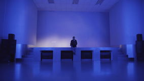 A young man sits alone on an empty dance floors and uses laptop to invite friends to a party.  stock video footage