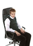 The young man sits in an armchair Royalty Free Stock Image