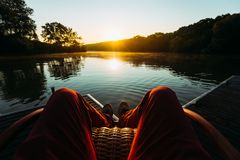 Young Man Sits In Armchair By The Lake And Meets Sunrise Or Sunset, Point Of View. Recreation Relaxation Concept. Young Man Sits In Armchair By The Lake And Royalty Free Stock Image
