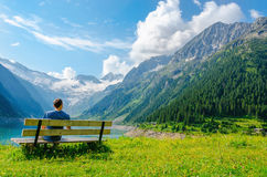 Young man sits on bench by azure mountain lake Stock Photo