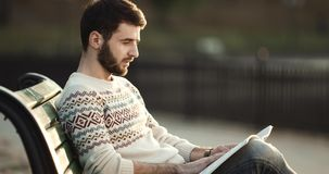 Young man sits on bench and with interest reads a book in a park. 4K stock video