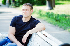 The young man sits on a bench Stock Photography