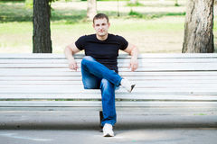 The young man sits on a bench Stock Images