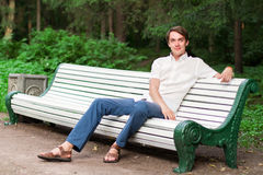 The young man sits on a bench Royalty Free Stock Photography