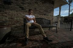 Young man sits on a bench. stock images