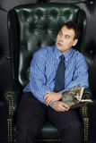Young man sits with book looks away in leather armchair Stock Photography