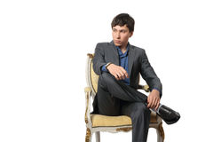 The young man sits in a chair. In a thoughtful pose on a white background royalty free stock photography