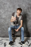 Young man sits on chair in empty room powdered with snow Royalty Free Stock Images
