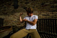 Young man sits on city bench flexing royalty free stock photos
