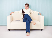 Young man sits comfortably on soft sofa Royalty Free Stock Image