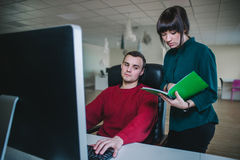 A young man sits at the computer in his chair and young woman standing next to him and show something in a notebook Stock Images