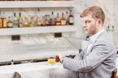 Young man sits at the counter of bar Royalty Free Stock Photography