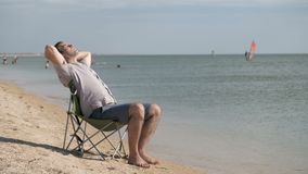 A young man sits on a deckchair by the sea and listens to music stock video footage