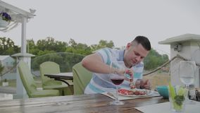 A young man sits down at a table in a terrace restaurant.. stock footage