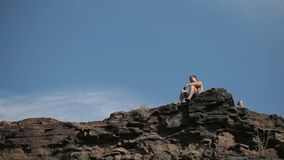 Young man sits on the edge of the cliff.  stock video footage