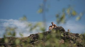 Young man sits on the edge of the cliff.  stock video