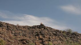 Young man sits on the edge of the cliff.  stock footage