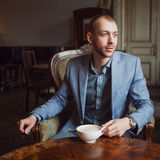 Young man sits and enjoys coffee in the morning. Portrait in the interior Stock Photo