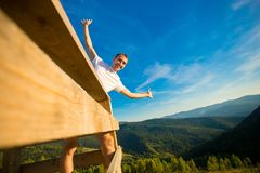 Young man sits on fence of wooden terrace and enjoy view of mountains. Young man sits on fence of wooden terrace and enjoy beautiful view of mountains royalty free stock images