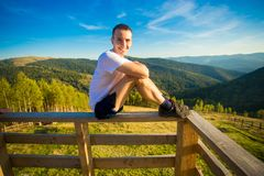Young man sits on fence of wooden terrace and enjoy view of mountains. Young man sits on fence of wooden terrace and enjoy beautiful view of mountains stock image