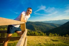 Young man sits on fence of wooden terrace and enjoy view of mountains. Young man sits on fence of wooden terrace and enjoy beautiful view of mountains royalty free stock photos