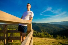 Young man sits on fence of wooden terrace and enjoy view of mountains. Young man sits on fence of wooden terrace and enjoy beautiful view of mountains stock images