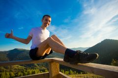 Young man sits on fence of wooden terrace and enjoy view of mountains. Young man sits on fence of wooden terrace and enjoy beautiful view of mountains stock photos