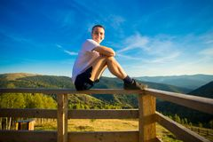 Young man sits on fence of wooden terrace and enjoy view of mountains. Young man sits on fence of wooden terrace and enjoy beautiful view of mountains royalty free stock photo