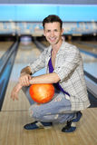 Young man sits on floor ball in bowling club Stock Images