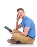 Young man sits on the floor and holds book Stock Photos