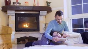 Married couple relaxes with tablet near fireplace. Young man sits on floor and young girl lays on his knees. People are relaxing near fireplace in living room stock video footage