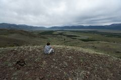 Young man sits on the hill stock photos