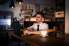 Young man sits in the kitchen at the bar counter and works in laptop Royalty Free Stock Photo