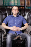 Young man sits in leather armchair Stock Photo