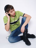 The young man sits and listens to music Stock Images