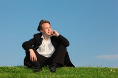 Young man sits on meadow against sky Stock Photos