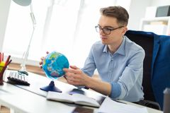A young man sits in the office at a computer desk, looks at the globe and thinks. stock photo