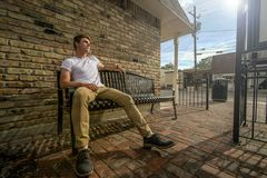Young man sits on outside bench. royalty free stock image