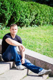 The young man sits in park Royalty Free Stock Photos