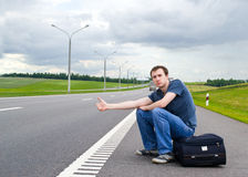 The young man sits pending on road with suitcase Royalty Free Stock Image