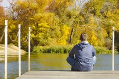 Young man sits on the pier. Autumn sunny day. Back view.  stock image
