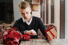 A young man sits in a restaurant and is waiting for a meeting with a girlfriend, girlfriend or wife. Flowers and a gift. Are near, looking at the clock royalty free stock image