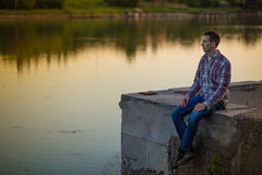 A young man sits on the river bank Stock Image