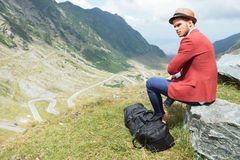 Young man sits on rock with his bag Stock Images