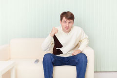Young man sits on sofa and watches football on TV Stock Photos